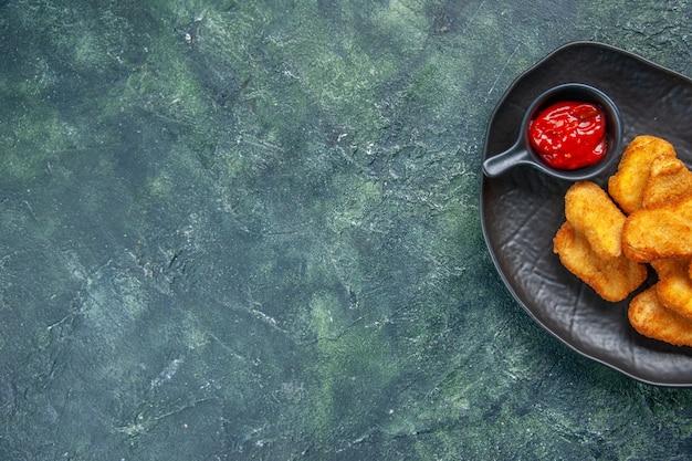 Halbe aufnahme von leckeren chicken nuggets und ketchup in schwarzer platte auf der linken seite auf dunkler oberfläche mit freiem platz