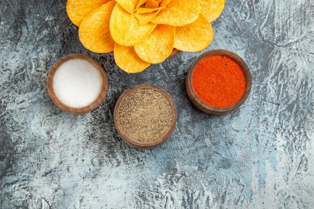Halbe aufnahme von leckeren kartoffelchips, dekoriert wie blumen und verschiedene gewürze auf grauem tisch