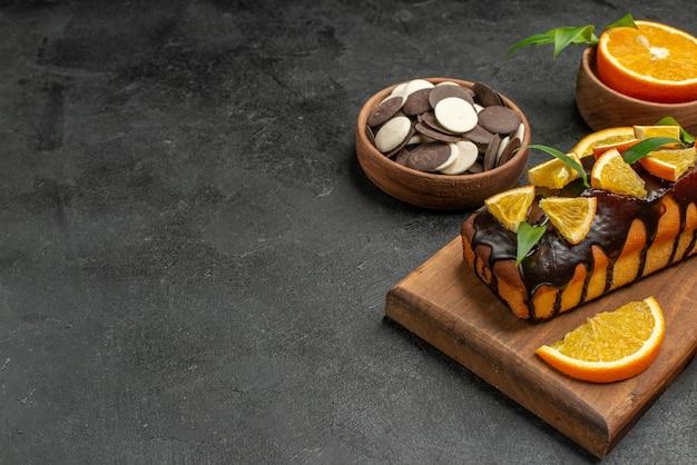 Halbe aufnahme von leckeren kuchen schneiden orangen mit keksen auf schneidebrett auf dunklem tisch