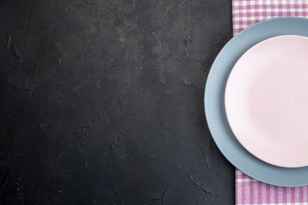 Halbe aufnahme von weißen und blauen keramikplatten auf gefaltetem rosafarbenem handtuch auf schwarzem hintergrund mit freiem platz