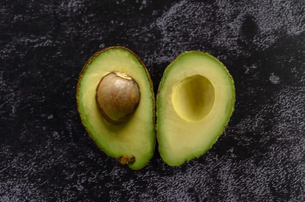 Halbe avocado auf dem schwarzen zementboden.