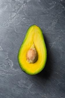 Halbe avocado auf dunklem hintergrund. biolebensmittelkonzept.