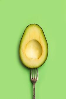 Halbe avocado mit einer gabel auf grünem hintergrund