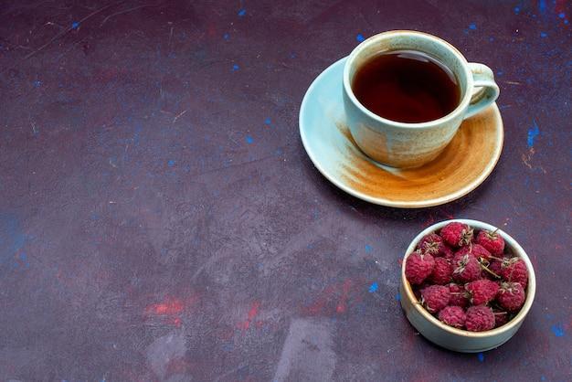 Halbe draufsicht auf eine tasse tee mit frischen himbeeren auf dunkler oberfläche
