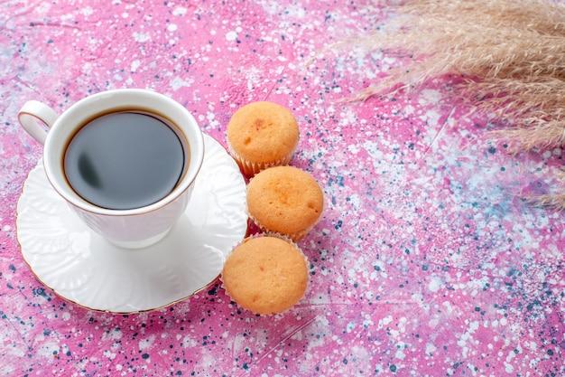 Halbe draufsicht auf eine tasse tee mit kleinen kuchen auf der rosa oberfläche