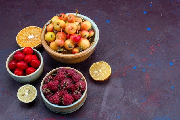 Halbe draufsicht auf frische früchte himbeerpflaumen in platten auf dunkler oberfläche
