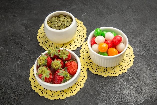 Halbe draufsicht frische erdbeeren mit bunten bonbons auf dem dunklen hintergrund fruchtbeerenfarben-regenbogenbonbons