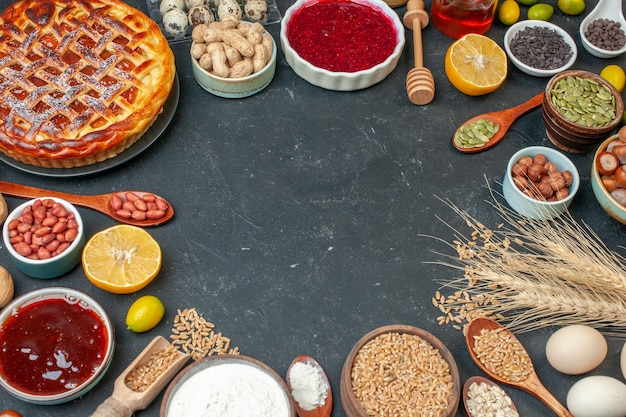 Halbe draufsicht leckerer fruchtiger kuchen mit eiern und nüssen auf dunklem tisch