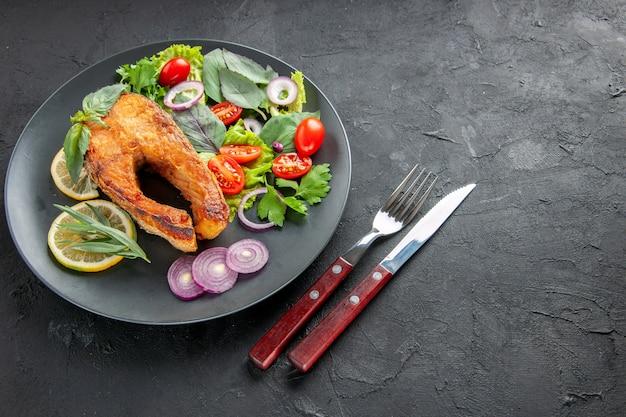 Halbe draufsicht leckerer gekochter fisch mit frischem gemüse und besteck auf dunklem hintergrund essen foto gericht rohe farbe fleisch meeresfrüchte