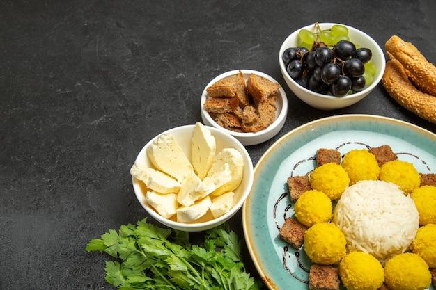 Halbe draufsicht süße leckere bonbons mit weißem käse und trauben auf dunklem hintergrund früchte süßigkeiten tee süße leckereien süß