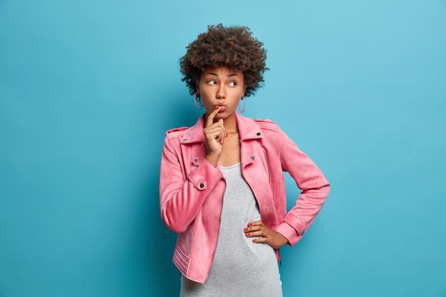 Halbe einstellung eines nachdenklichen jungen weiblichen models mit lockigem haar, hält den zeigefinger auf den lippen, schaut nachdenklich zur seite, denkt über die richtige entscheidung nach, trägt ein graues kleid und eine rosa jacke, erinnert sich an etwas