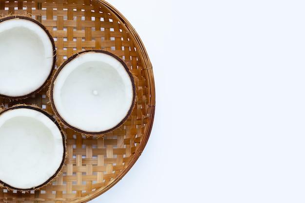 Halbe kokosnüsse auf hölzernem bambusdreschkorb auf weißer oberfläche