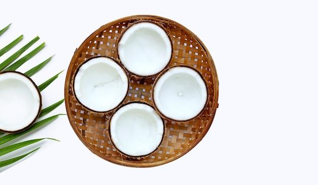 Halbe kokosnüsse auf hölzernem bambusdreschkorb auf weißer wand. speicherplatz kopieren