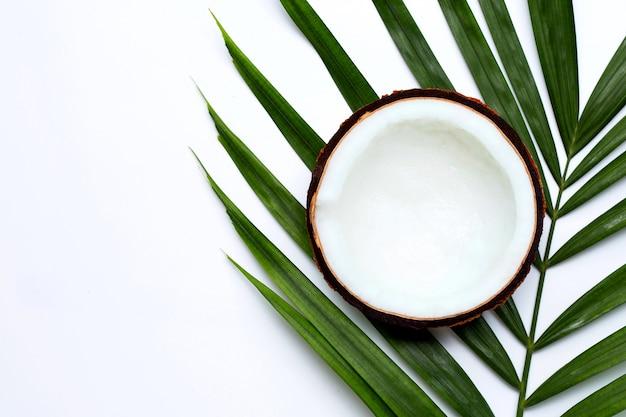 Halbe kokosnuss auf tropischen palmblättern auf weißem hintergrund. draufsicht