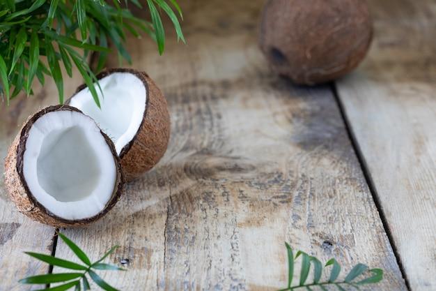 Halbe kokosnuss und palmzweig liegen auf holztisch.