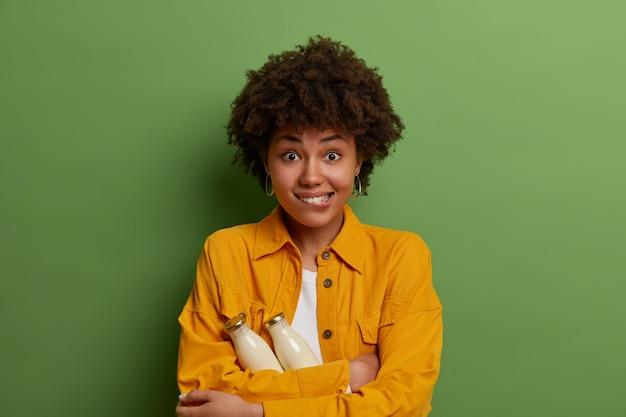 Halbe länge aufnahme von positiven afroamerikanischen frau beißt sich auf die lippen, hält zwei glasflaschen pflanzliche milch, trinkt nur bio-getränke, hält sich gesund, trägt gelbes hemd, steht drinnen