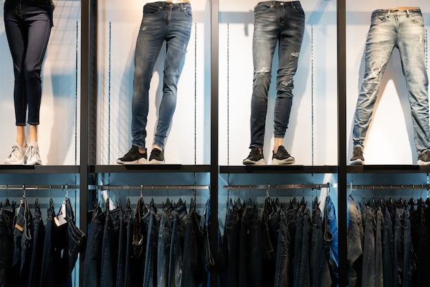 Halbe männliche schaufensterpuppen gekleidet in jeans im laden und jeanshosen in einer reihe.