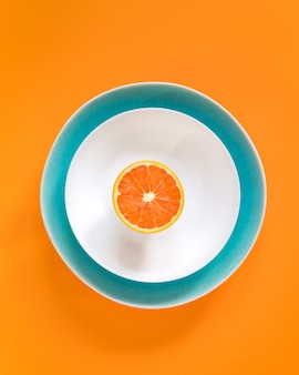 Halbe orange auf einem teller. draufsicht, flach zu legen