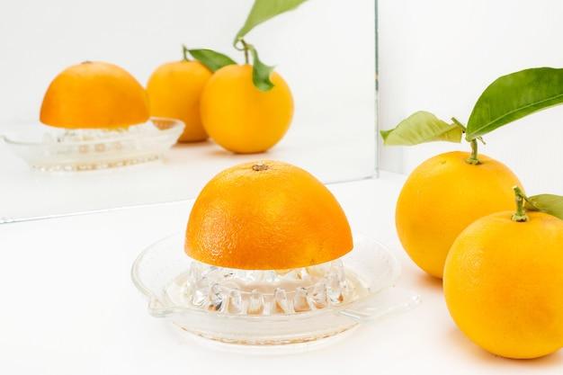 Halbe orange auf einer presse und zwei orangen mit blättern