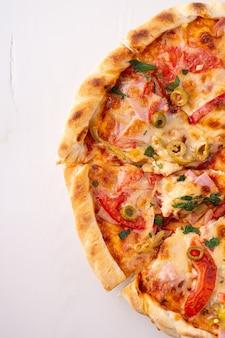 Halbe pizza auf weißer hölzerner hintergrundkopierraum-draufsicht