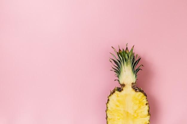 Halbe scheibe der schönen frischen appetitlich leckere ananas auf rosa hintergrund. draufsicht. horizontal. text kopieren konzeptionell