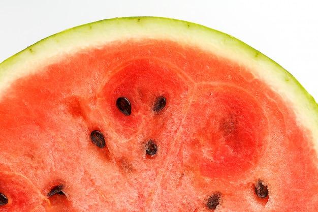 Halbe scheiben der geschmackvollen und reifen roten wassermelone auf einer weißen, lokalisierten beschaffenheit der saftigen masse der reifen roten wassermelone mit samen