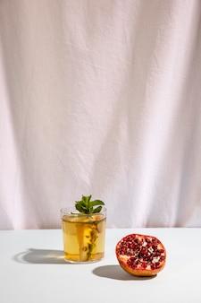 Halber granatapfel mit köstlichem getränk auf tabelle
