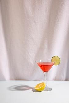 Halber kalk mit cocktailgetränk schmücken mit cocktail auf schreibtisch gegen lokalisiert auf weißem hintergrund