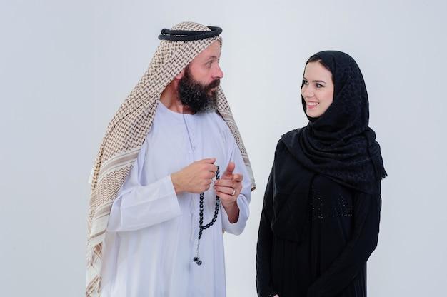 Halber körper des arabischen paares, das zusammen auf grauem hintergrund lokalisiert aufwirft.