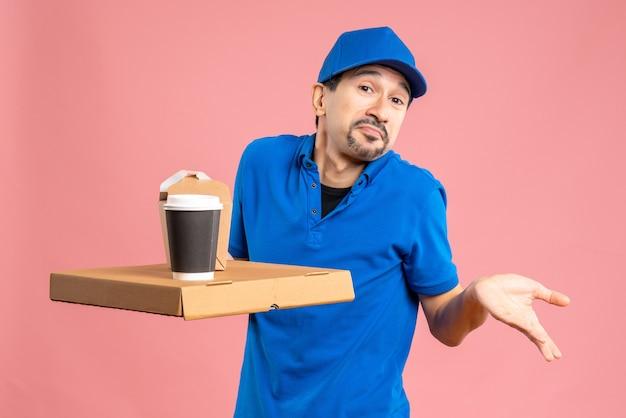 Halber körperschuss eines männlichen lieferers mit hut, der befehle erteilt und sich auf pastellfarbenem pfirsichhintergrund verwirrt fühlt