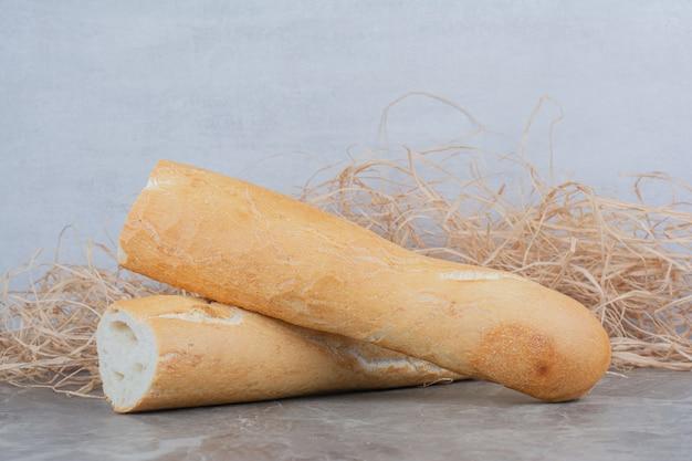 Halber schnitt von französischem baguette auf marmoroberfläche