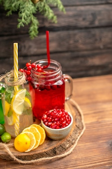 Halber schuss bio-frischsäfte in flaschen, serviert mit tuben und früchten auf einem holzbrett
