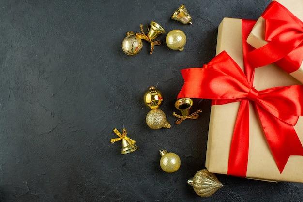 Halber schuss der geschenkbox mit rotem band und dekorationszubehör auf dunklem hintergrund
