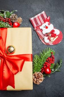 Halber schuss der weihnachtsstimmung mit schönen geschenken mit bogenförmigem band und tannenzweigdekorationszubehör-weihnachtssocke auf vertikaler ansicht des dunklen hintergrunds