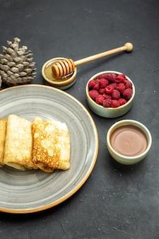 Halber schuss des abendessenhintergrundes mit köstlichem pfannkuchenhonig und schokoladenhimbeer- und nadelbaumkegel auf schwarzem hintergrund