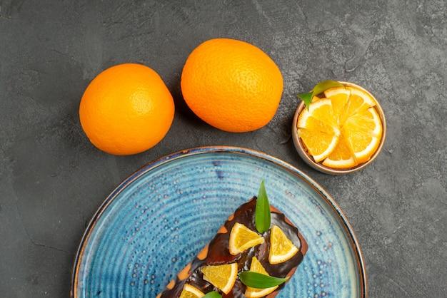 Halber schuss des köstlichen kuchens und der zitrone auf horizontaler ansicht des schwarzen tisches