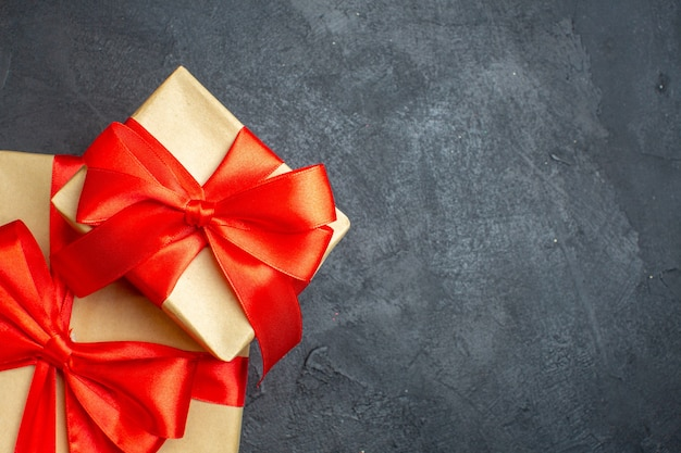 Halber schuss des weihnachtshintergrundes mit schönen geschenken mit bogenförmigem band auf der rechten seite auf einem dunklen hintergrund