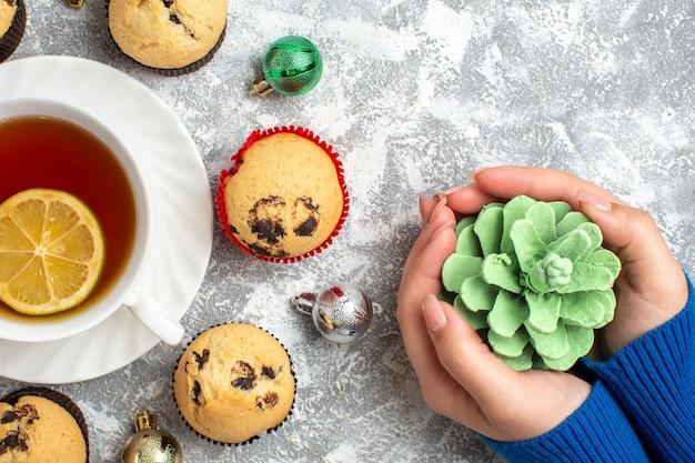 Halber schuss einer tasse schwarzen tee mit zitrone unter frisch gebackenen köstlichen kleinen cupcakes und dekorationszubehör und hand, die nadelbaumkegel auf eisoberfläche hält