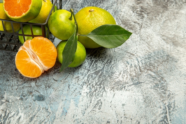 Halber schuss eines korbes voller frischer grüner mandarinen und halbierter mandarine auf grauem hintergrund