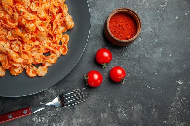 Halber schuss einfaches nudelgericht zum abendessen auf einem schwarzen teller und gabelpfeffer und tomaten auf dunklem hintergrund