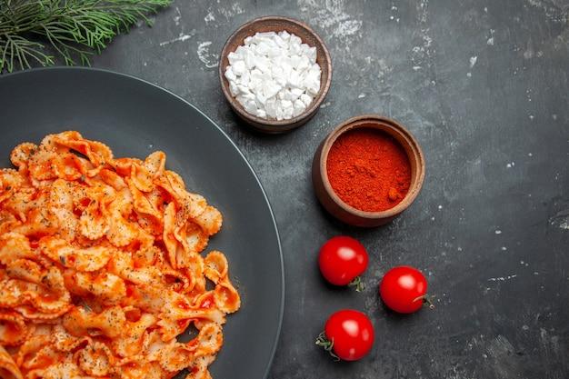 Halber schuss einfaches nudelgericht zum abendessen auf einem schwarzen teller und verschiedenen gewürzen und tomaten auf dunklem hintergrund