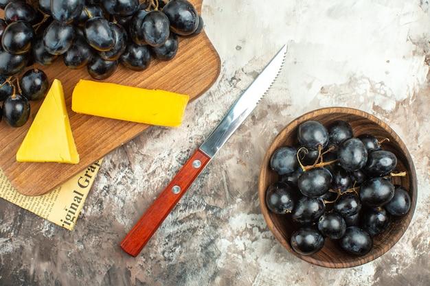 Halber schuss frischer köstlicher schwarzer trauben und käse auf holzbrett und in einem braunen topfmesser auf gemischtem hintergrund
