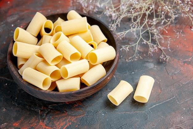 Halber schuss in nahaufnahme von ungekochten nudeln innerhalb und außerhalb des braunen topfes auf schwarzem tisch