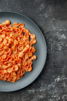 Halber schuss köstliche pasta-mahlzeit auf einem schwarzen teller zum abendessen auf der rechten seite auf dunklem hintergrund