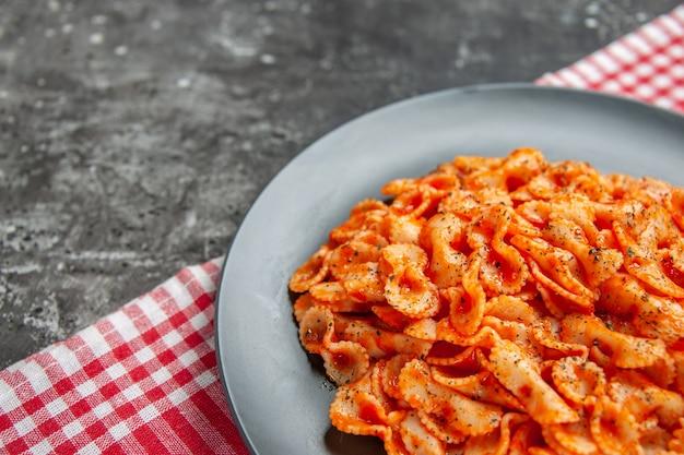 Halber schuss köstliche pasta-mahlzeit auf einem schwarzen teller zum abendessen auf einem rot gestreiften handtuch to