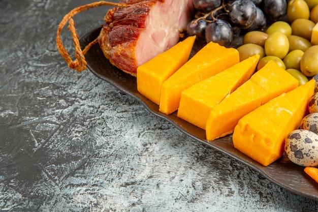 Halber schuss köstlichen besten snacks für wein auf braunem tablett auf grauem hintergrund