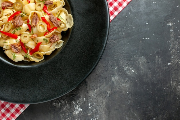 Halber schuss köstlicher conchiglie mit gemüse auf einem schwarzen teller und messer auf rotem, abgestreiftem handtuch auf grauem tisch