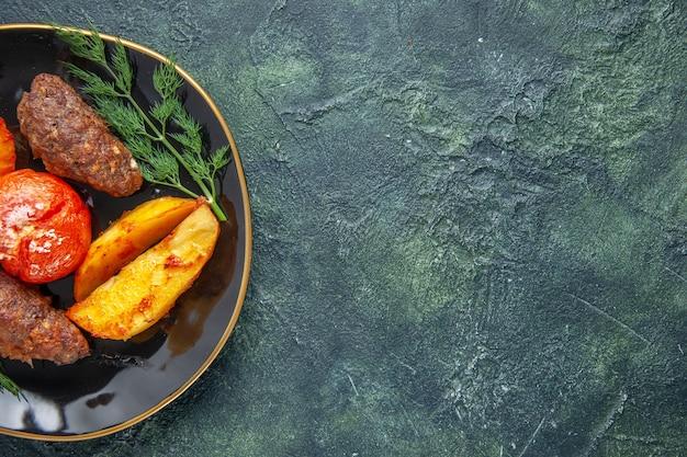 Halber schuss köstlicher fleischkoteletts, gebacken mit kartoffeln und tomaten auf einem schwarzen teller auf der rechten seite auf grün-schwarzem mischfarbhintergrund