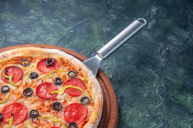 Halber schuss köstlicher hausgemachter pizza auf holzbrett auf der rechten seite auf dunkler oberfläche