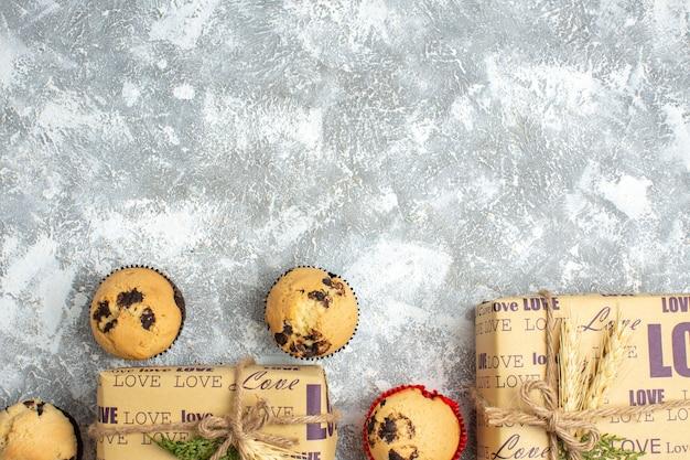 Halber schuss köstlicher kleiner cupcakes mit schokolade um geschenk mit liebesaufschrift auf eistisch
